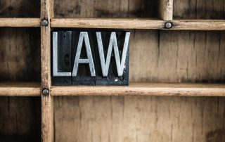 "photo of The word ""LAW"" written in vintage metal letterpress."