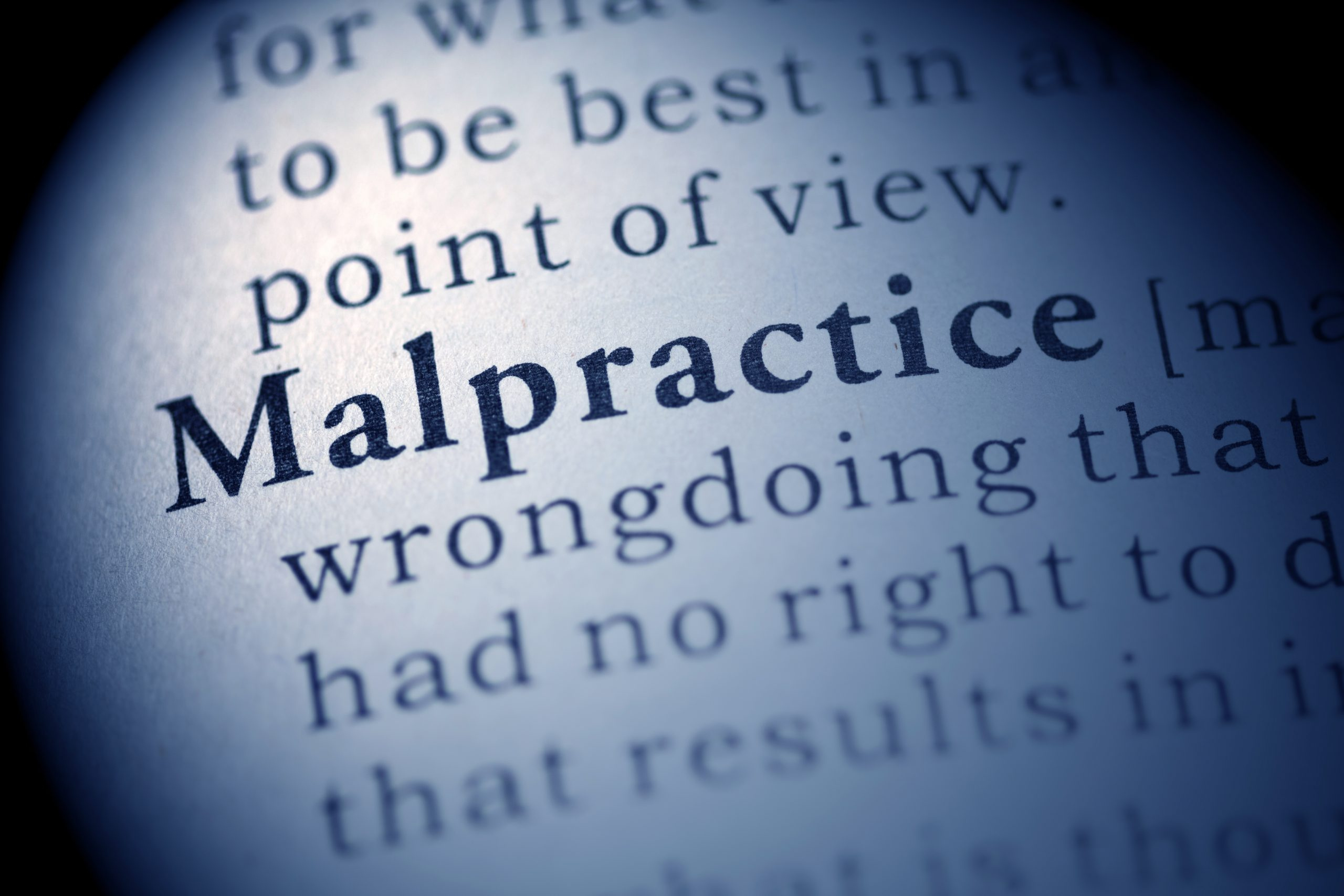 photo of the word Malpractice in a dictionary.