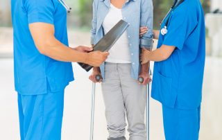 photo of friendly healthcare workers with injured woman on crutches in hospital
