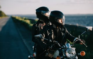 photo of of bikers in helmets riding classical motorcycle on country road