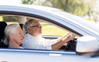 photo of senior couple driving in a car