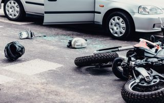 a motorcycle and car on the street after motorcycle accident