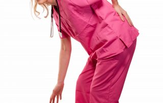 photo of lady nurse healthcare worker bent over with a hand on the lower back with a pained expression