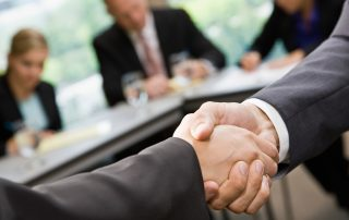 two people shaking hands in conference room