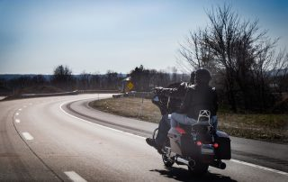 photo of a couple on a motorcycle ride on highway