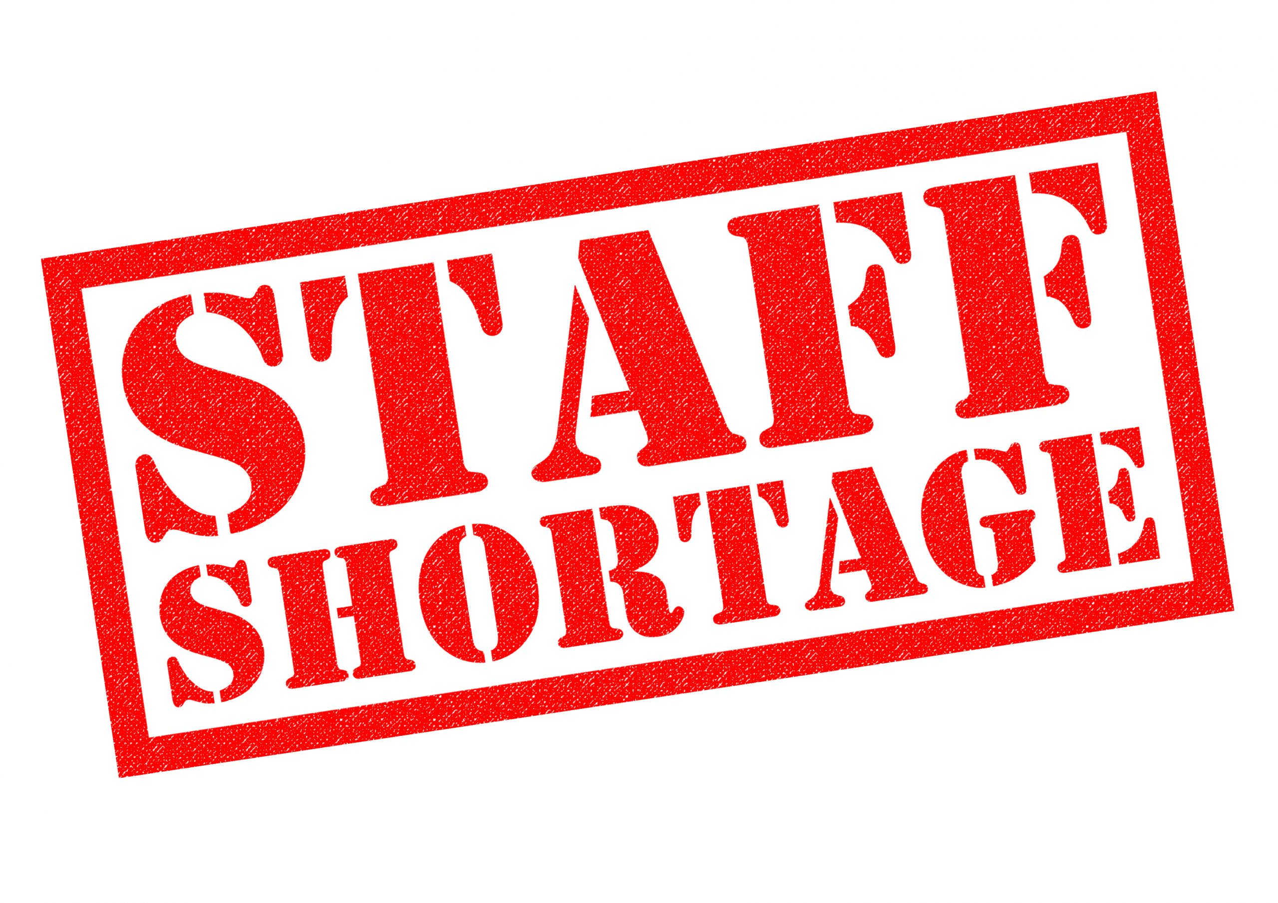 photo of STAFF SHORTAGE red Rubber Stamp over a white background.