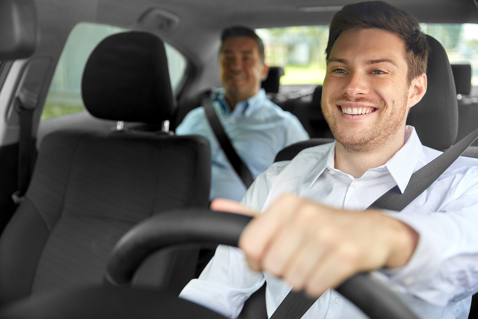photo of a happy smiling male driver driving car with the passenger