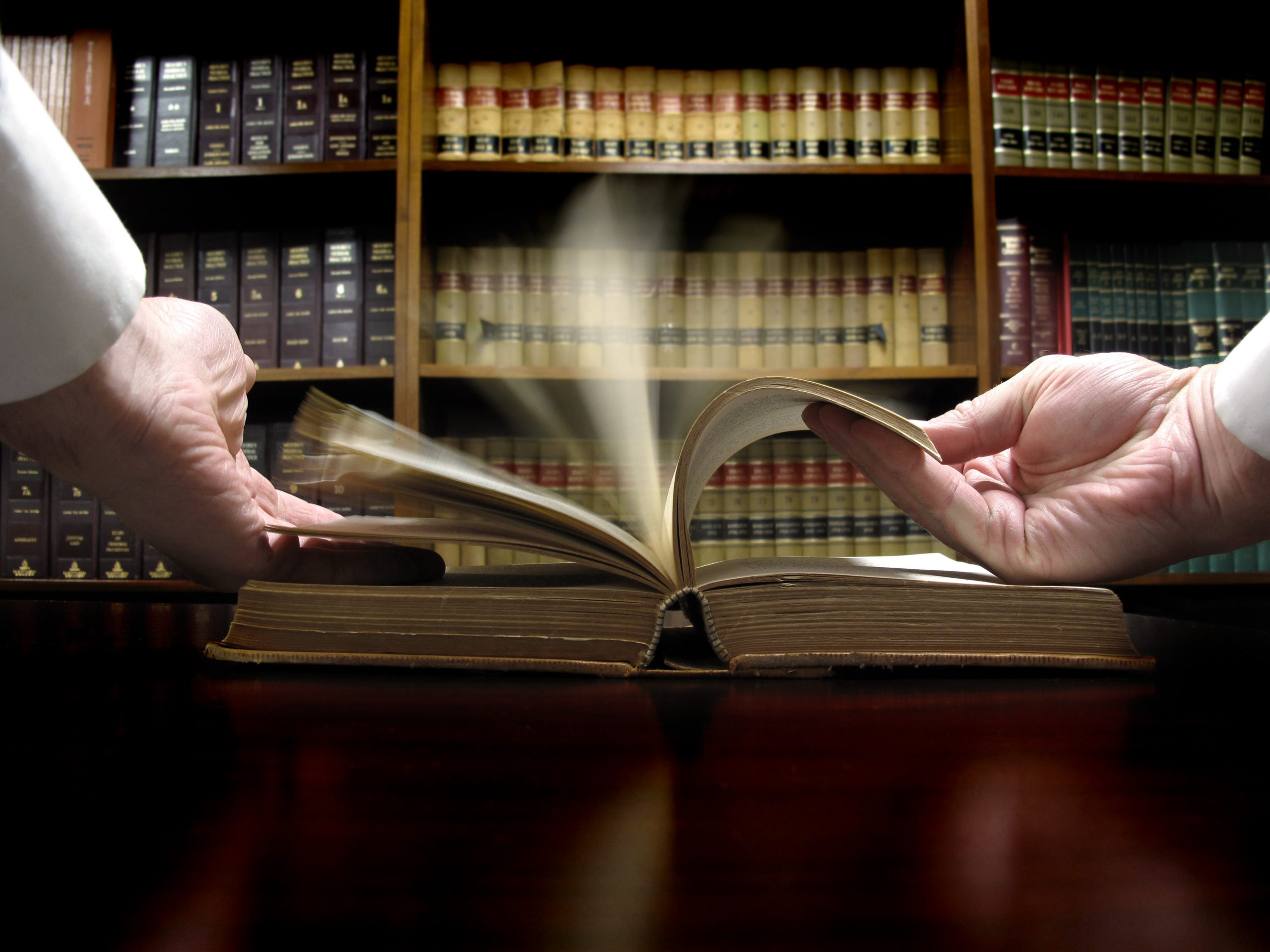 photo of Hands turning pages in old law book