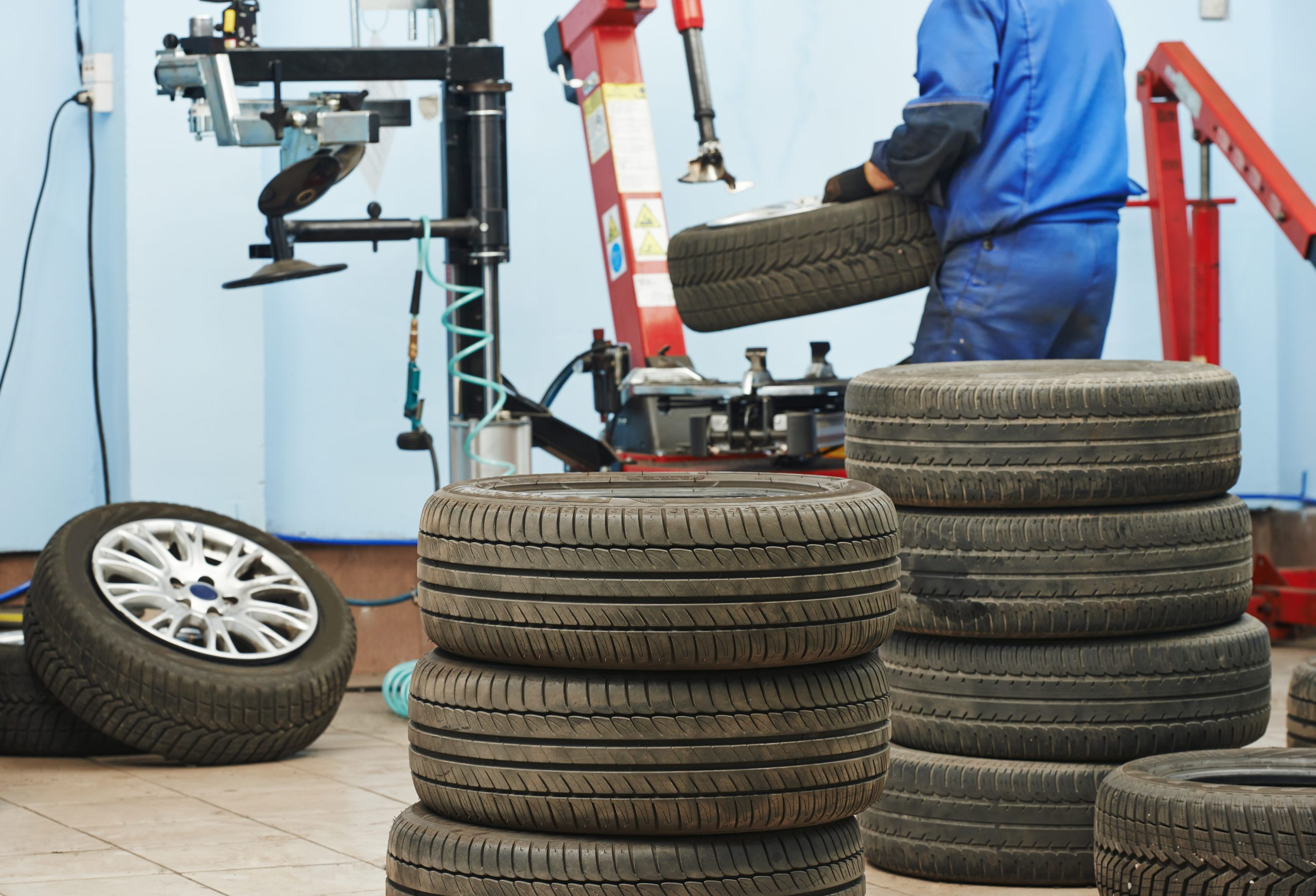 photo of Auto repairman loading automobile car wheel at tire fitting machine during tire replacing