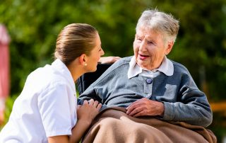 photo of Nurse holding hands with senior woman