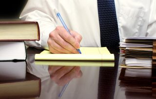 photo of Business Man sitting at desk holding pen with files