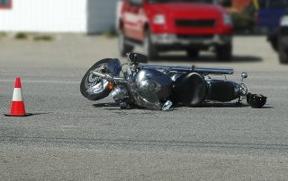 picture of a damaged motorcycle laying on the road after the accident