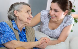 photo of a woman holding hands with an old lady showing care