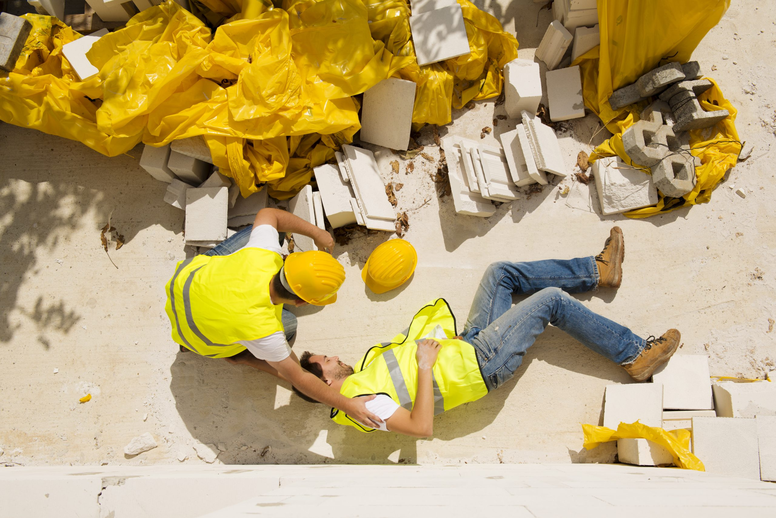 a construction site where one construction worker is injured and another is helping him